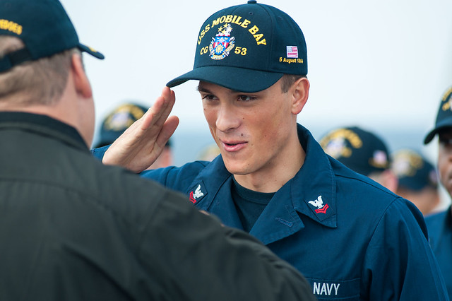 Cryptologic Technician (Technical) 2nd Class Daniel Carns, from Seattle, salutes Capt. Thomas Halvorson