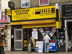 "A terraced shopfront with a yellow sign reading ""Western Centre / Western Union / Money Transfer / Bureau de Change / Cheque Cashing / Fax / Photocopying / Printing / Scanning / Computer & Laptop Sales & Repair / Tel: 020 8688 5558 / DHL Service Point / Send & Pickup Your Parcel From Here""."