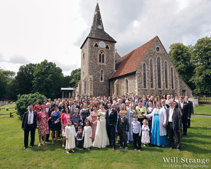 Photograph of entire wedding party in front of the church