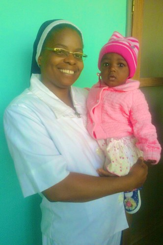 Martina Ariyo SSL carrying a baby at the a special celebration party for children at the Centre de Santé St Louis
