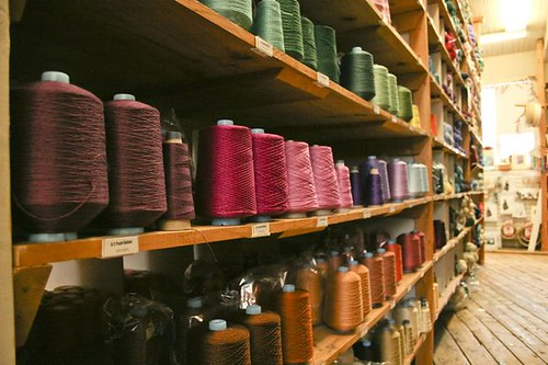 long shelves holding spools of colorful yarn
