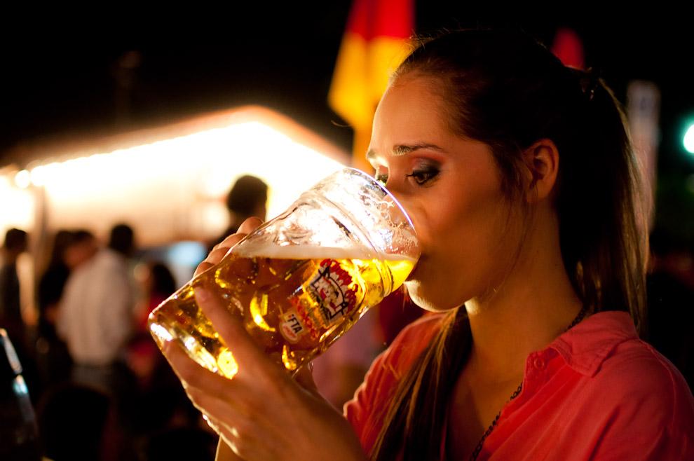 """Una asistente bebe cerveza de la manija de 2 litros mientras escucha la orquesta musical """"Chopao"""" frente al Salón Social del Club Alemán de Colonia Obligado, la noche del 10 de Noviembre. (Elton Núñez)"""