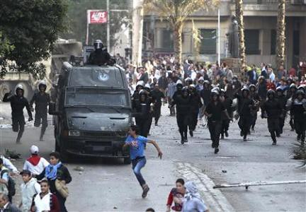 Egyptian riot police chase demonstrators in Cairo amid anti-dictatorship protests in November 2012. Thousands are opposing the Muslim Brotherhood government. by Pan-African News Wire File Photos