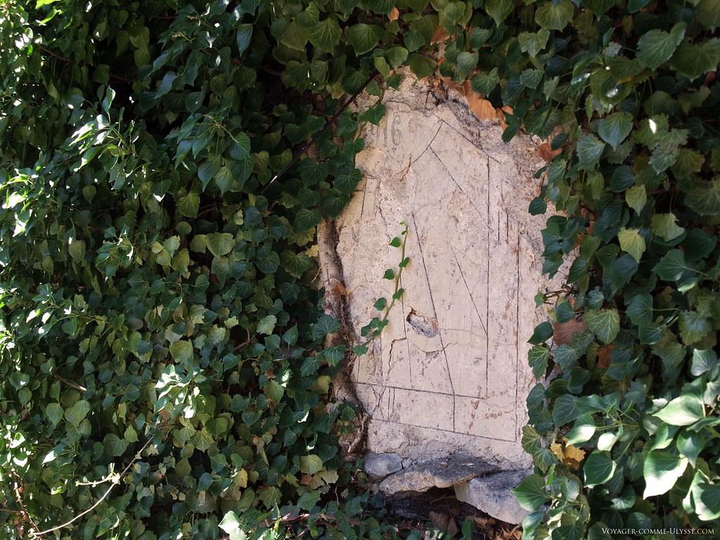 Le cadran solaire, datant de 1916, enfoui sous les feuilles des plantes grimpantes.