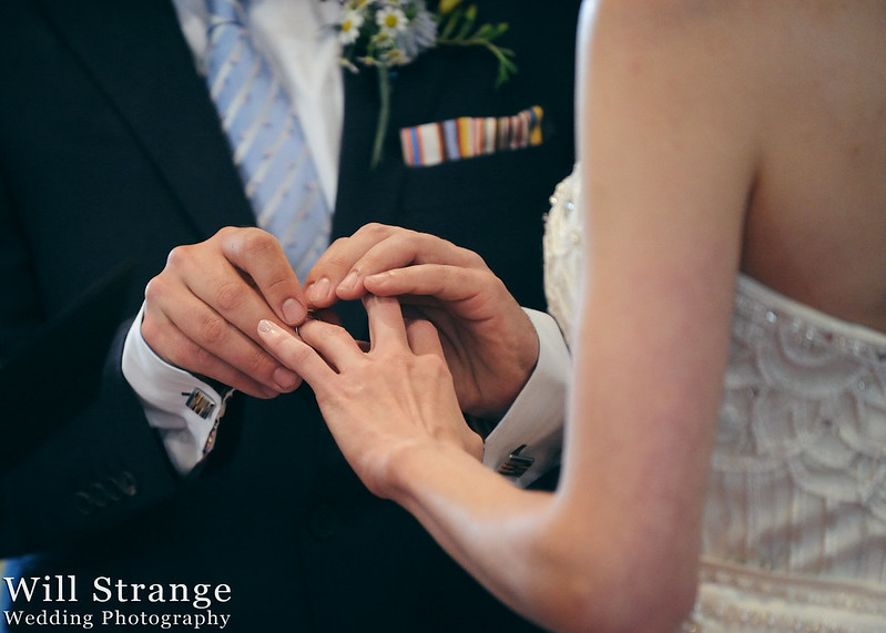 Groom places ring on bride's hand
