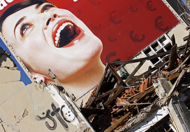 Part of an advertising billboard announcing discounts in euros is seen over a ruined old factory on the outskirts of Lisbon