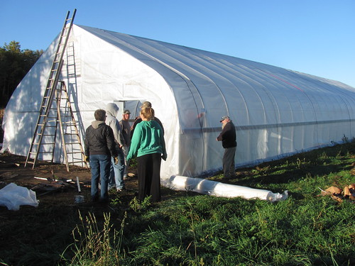 A group finishes putting the outer skin on a hoop house in Michigan. The hoop house has helped local farmers lengthen the short Michigan growing season by two full months, giving them additional crops to sell at winter markets.  Photo courtesy Brittain Family Farms.