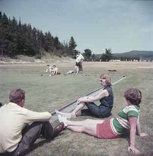 One man and two women sitting on the grass watching a lawn bowling game, Fundy National Park, New Brunswick / Un homme et deux femmes assis sur le gazon observent une partie de boulingrin, dans le parc national Fundy (Nouveau-Brunswick)