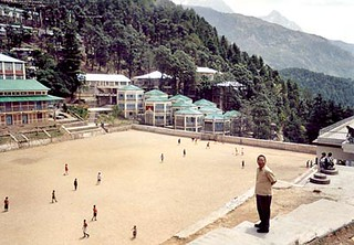 Thupton Dorjee stands above a group of Tibetan  children playing soccer in the TCV.