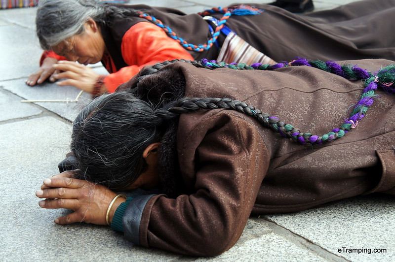 Locals praying while lying on the ground