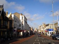 A view along a street with buildings of varying styles and heights on each side. The sky is a clear blue with a few clouds.  Bus lanes run along each side of the street.