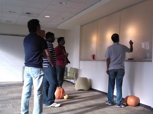 Sr program manager, pumpkins at his feet shares insights on Excel 2013, planning a new application, giving instruction on transparent lighted panels, to a group of programers, program managers, consultants, Redmond Town Center, Washington, USA by Wonderlane