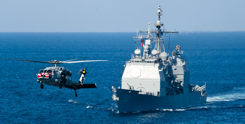 MH-60S Sea Hawk helicopter of Eightballers of Helicopter Sea Combat Squadron (HSC) 8 flies past t USS Mobile Bay