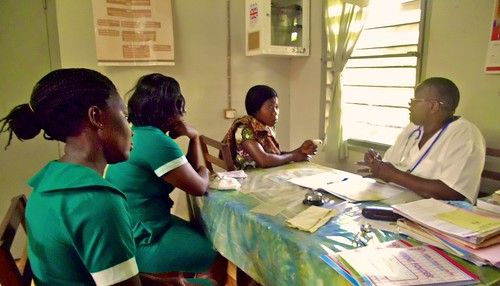 Esther Adzah SSL with some of the health centre nurses in consultation with a patient at St John's Health Centre, Domeabra, Ghana