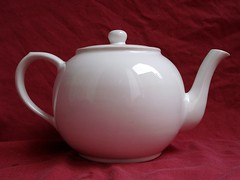 Side-on view of a large white ceramic teapot against a burgundy background.