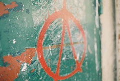 An anarchy symbol painted on the side of the door. Symbols like this are common all over Paris.