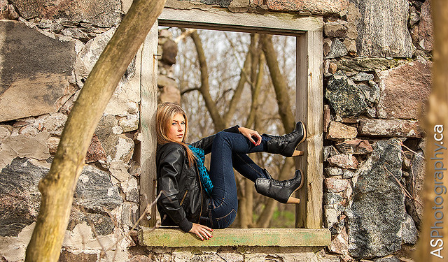 Beautiful blonde woman in jeans in a stone window.