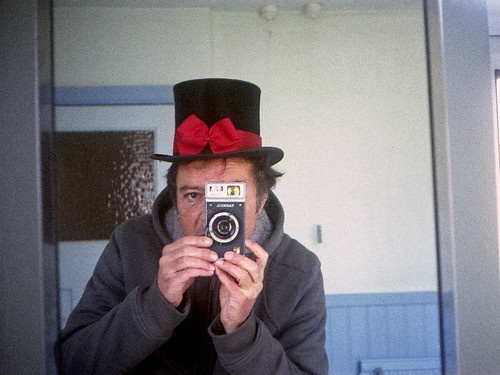 reflected self-portrait with Yashica Rapide camera and bowed top hat by pho-Tony