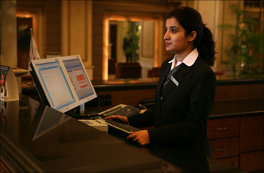 Rabia, a former Hashoo Foundation trainee at Pearl Continental Hotel in Rawalpindi, works at the front desk after she was hired by the hotel.