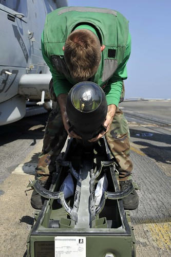 A Sailor puts away a Hellfire missile.