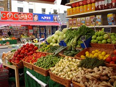 A view from just within an open shopfront showing a display of vegetables including red peppers, okra, scotch bonnet chillies, and leafy greens, in front of shelves of packaged African foods such as fufu mix and palm oil.  Another similar shop is visible across the street.