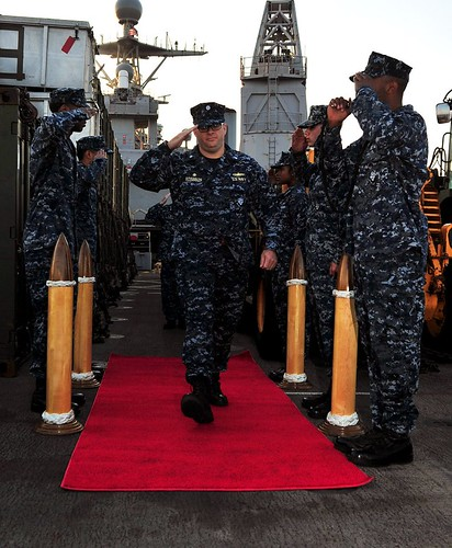 Cmdr. Tate Robinson passes through ceremonial sideboys before relieving Cmdr. Brian Finman