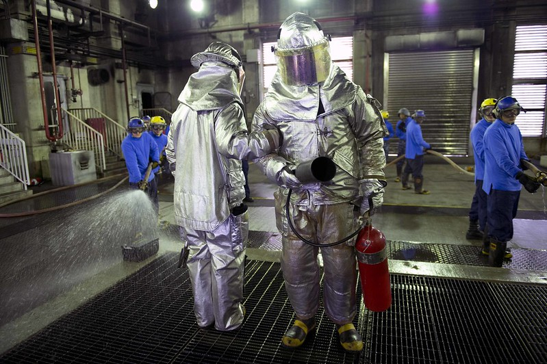 Sailors dressed in firefighting proximity suits, perform an overhaul during a flight deck fire drill