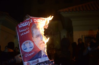 A protester burns a campaign poster that belongs to presidents to president muhammad morsi
