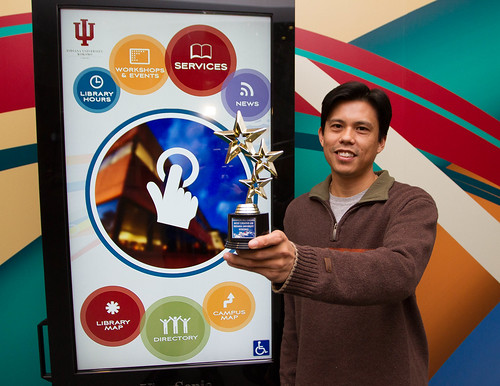 Ed Ventura infront of the digital sign that earned the UITS team the Cassie award