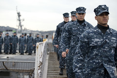 Sailors cross the brow during a hull swap ceremony between the guided-missile cruisers USS Cowpens (CG 63) and USS Antietam (CG 54), Feb. 5 in Yokosuka, Japan. (U.S. Navy photo by Mass Communication Specialist 3rd Class Paul Kelly)