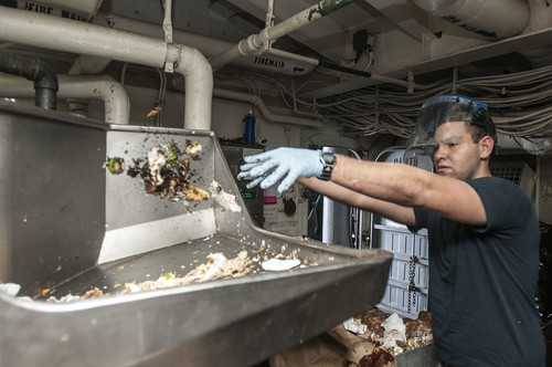 Aviation Ordnanceman Airman Chris Lewis sorts food trash in the pulping room
