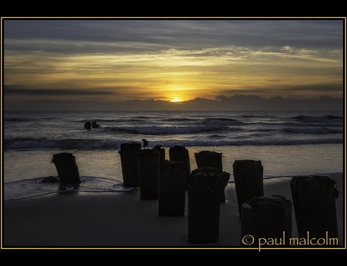 ocean sky sun beach water clouds sunrise nc northcarolina pilings atlanticocean carolinabeach canon1635mmf28l newhanovercounty paulmalcolm