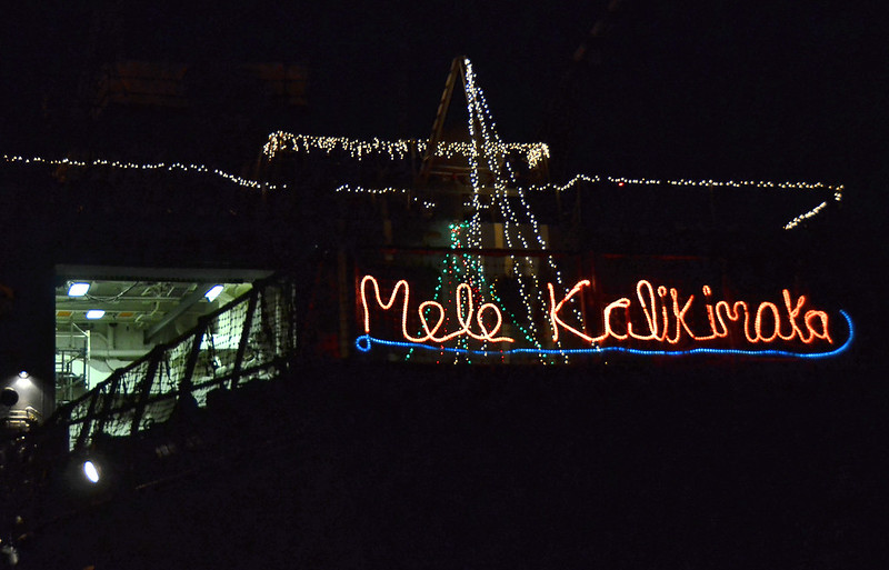 "Holiday lights with the Hawaiian phrase ""Mele Kalikimaka"" (Merry Christmas) are displayed on USS Chung-Hoon"