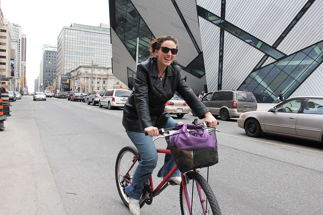 Image of a woman riding bike in city street in front of building with post-modern architecture.