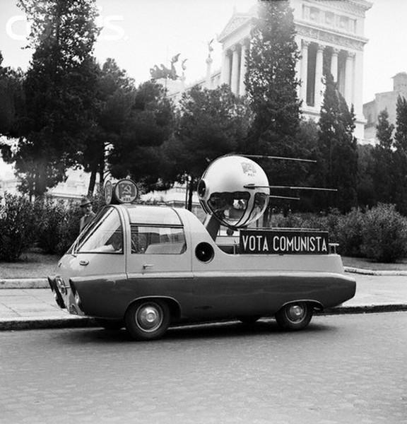 """ROMA BENI CULTURALI - I FORI IMPERIALI - VIA DEI FORI IMPERIALI (1958): """"VOTA COMUNISTA"""", Piccola automobile del partito comunista parcheggiato lungo la Via dei Fori Imperiali nel 1958."""