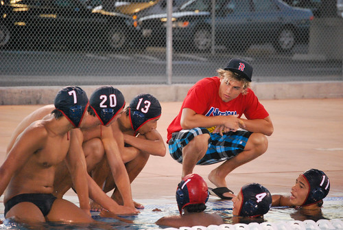 Boy  #3 crouched down talking to his water polo team mates.