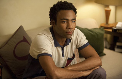 Donald Glover, as Sandy, sits on a couch