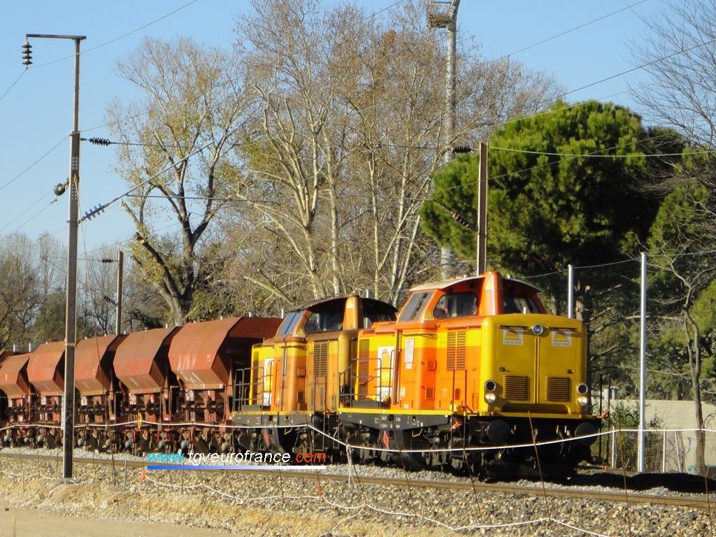 Vue détaillée des deux locomotives thermiques V100 tractant des wagons de transport de ballast