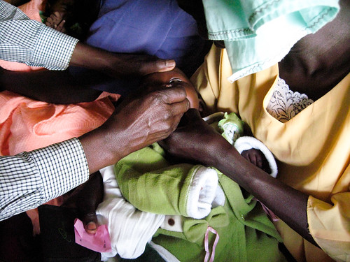 A mother holds her young baby while a community health worker gives him his oral polio vaccine.  Great Rift Valley Region, Kenya