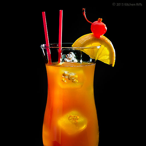 Hurricane Cocktail in Hurricane Glass with Orange and Cherry Garnish