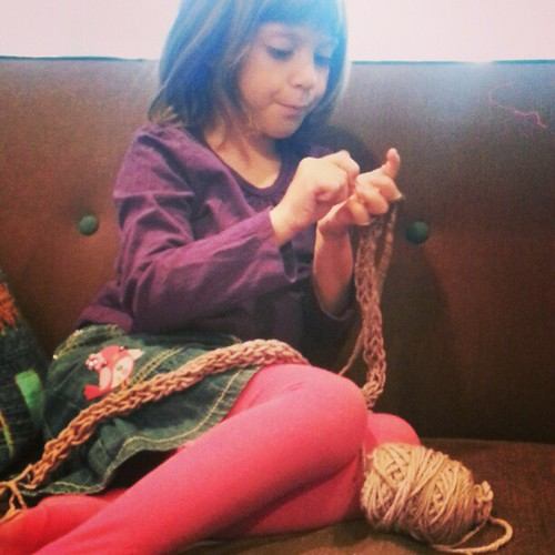 Ada, finger knitting a scarf for her teacher.