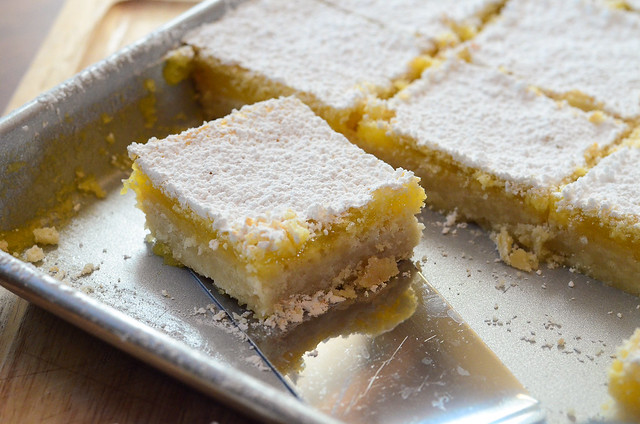 A spatula lifting a slice of lemon bar.