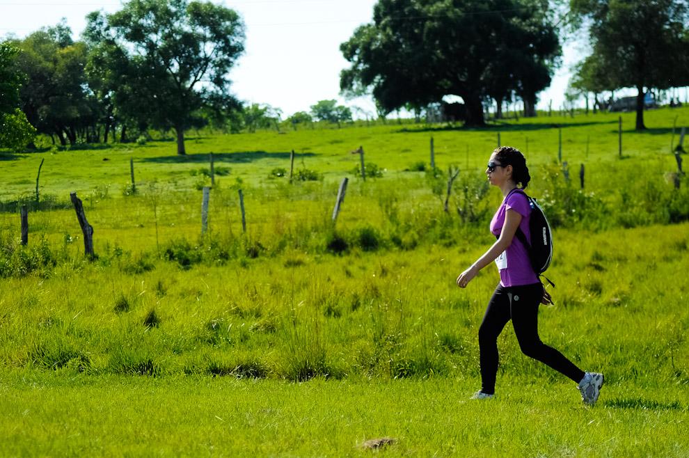 Una participante atravesando los campos verdes de la Quinta Mandu'arã, minutos antes de comenzar la carrera. (Elton Núñez)