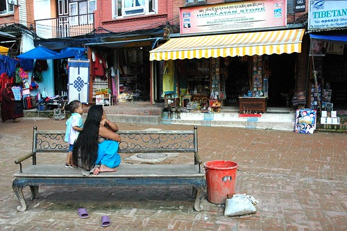 Long haired woman and child on a bench in front of Himalayan Store, purple shoes, Tibetan door cover, infinity knot, red bucket, near the Great Wish Fullfilling Stupa, markets, Boudhanath, Kathmandu, Nepal by Wonderlane