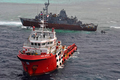 Malaysian tug Vos Apollo, foreground, prepares for defueling operations Jan. 24 near the grounded USS Guardian (MCM 5) while a U.S. Navy small boat approaches with a salvage team. (U.S. Navy photo by Aircrewman 3rd Class Geoffrey Trudell)
