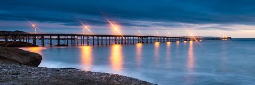 ocean sunset reflection beach water clouds pier rocks illumination coastline centralcoast avila