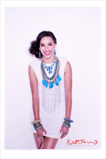 Model in white dress wearing chunky blue beaded antique style bracelets teamed with beaded necklaces with feather details and matching earings. Photography by Kent Johnson.