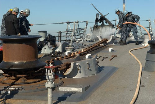 Sailors aboard USS STERETT (DDG 104) hose down and recover the anchor after successfully completing a precision anchorage while