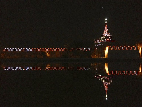the palace of Mandalay lit up at night. reflections in the moat.