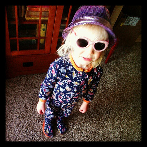 Sequined hat, pink rhinestone shades, rocketship footie pajamas. The girl's got style.